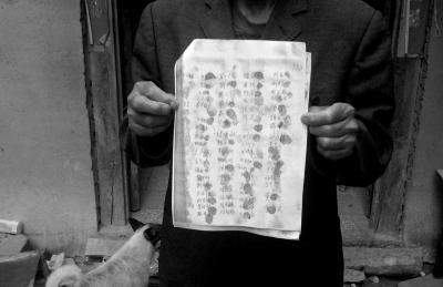 候见志父亲展示村民们的联名请愿书。
