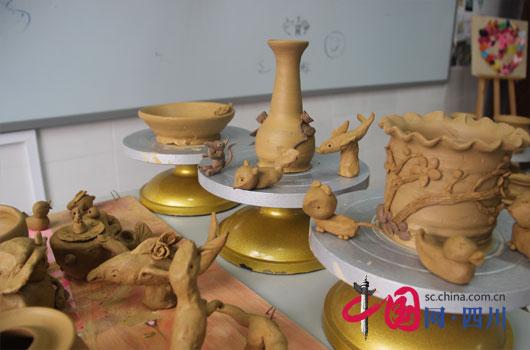 或揉或捏,或压或卷,或堆或雕,一堆堆小小的陶泥变成了笔筒,盘子,恐龙