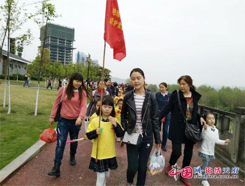 孩子们在老师带领下,举著红旗,走出幼儿园